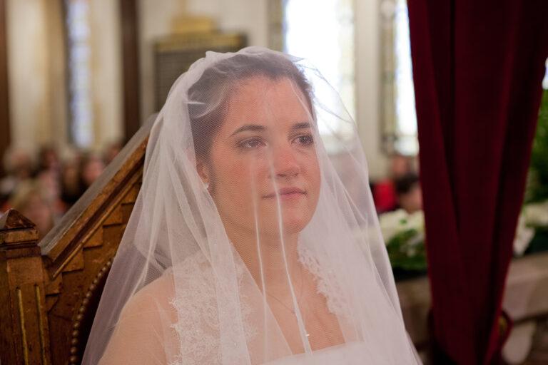 mariée sous son voile pendant la cérémonie